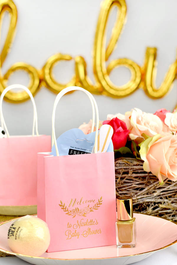 Cute and thoughtful mini kraft paper favor bags in New Pink with Gold imprint, custom printed with BS118 - Floral Welcome design and two lines of text in Lovable lettering style