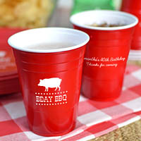 Red solo cups printed with White imprint, ABT110 design, and two lines of text on back of cups in Playful lettering style