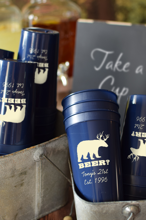 Navy 22 oz stadium cups printed with Ivory imprint, ABT134 design, and two lines of text in Playful lettering style
