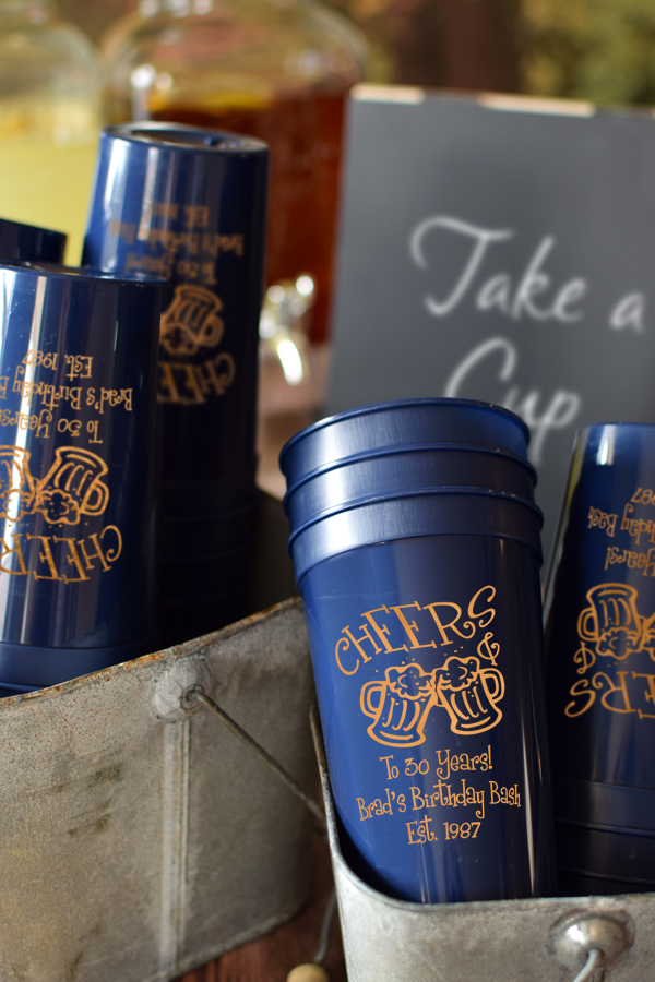 Navy 22 oz stadium cups printed with Copper imprint, ABT101 design, and three lines of text in Dimwit lettering style