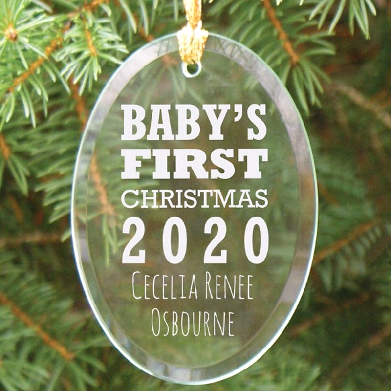 Baby's First Christmas oval glass ornament personalized with baby birth year and two lines of custom print for baby's name hanging on Christmas tree