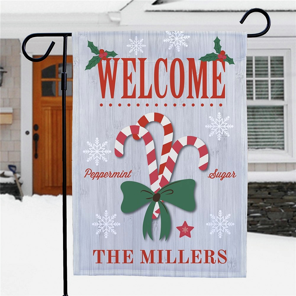 Christmas welcome garden flag displaying candy canes design personalized with family name