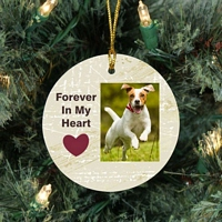 Round ceramic dog memorial Christmas ornament with picture of playing dog and phrase Forever In My Heart accented with Heart design