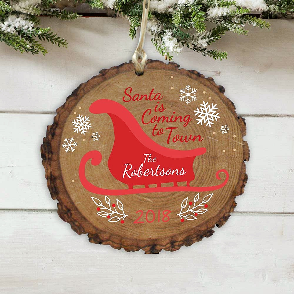 Round wood tree limb Christmas tree ornament personalized with 'Santa Is Coming To Town' phrase and family name on red Santa sleigh
