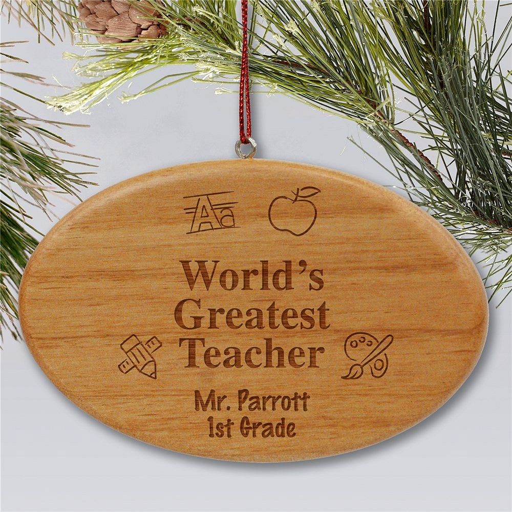 Oval shape wooden Christmas ornament personalized with 'World's Greatest Teacher' message, teacher's name and and grade with school theme graphics