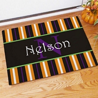 Fall theme welcome mat with orange, white purple and black stripes personalized with family named with family name