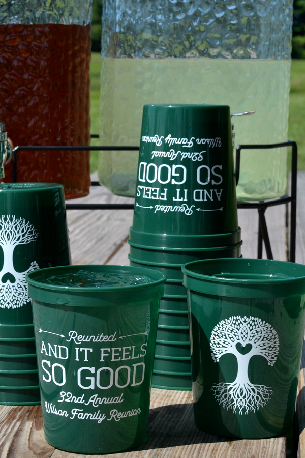 Personalized family reunion souvenir stadium cups, forest green with white imprint, design and two lines custom text on the front and large design on the back