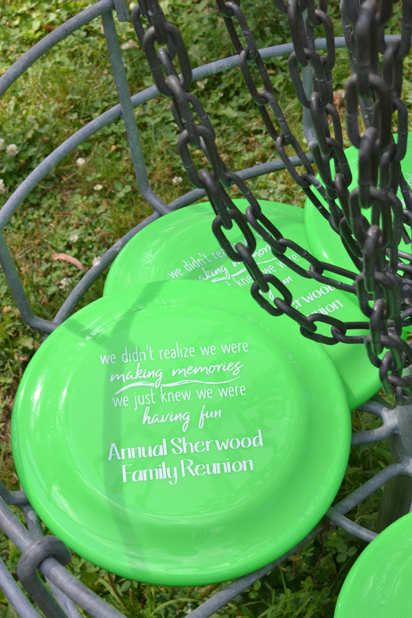 Personalized disc golf flying saucer favors in Neon Lime Green with family reunion design and custom text in White imprint