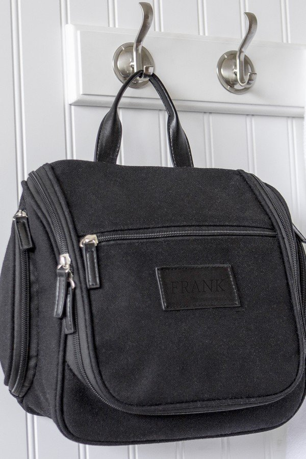 Men's black waxed canvas and leather hanging toiletry bag hanging on the door