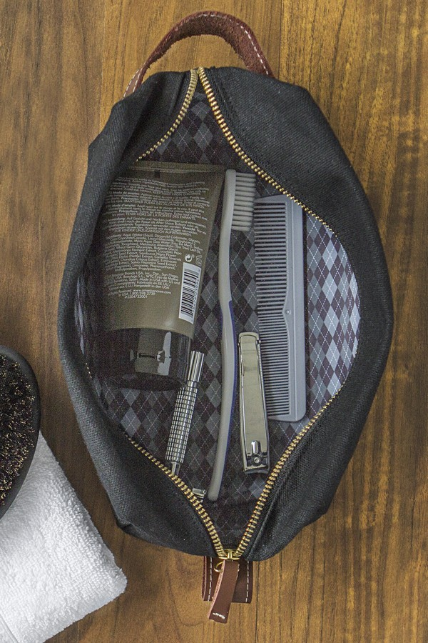 Opened view of men's wet waxed canvas and leather toiletry bag