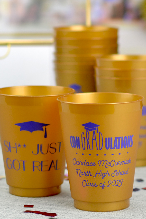 16 oz gold frosted graduation favor cup printed with Purple imprint color, G1215 and G1225 designs, and 3 lines of custom text in Garris lettering style