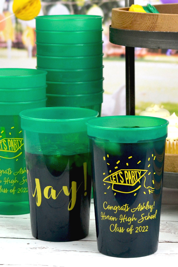 22 ounce translucent green stadium cups with yellow imprint, design g1219 - party cap and confetti on the front of the cups and design g1214 - yay on the back of the cups. The front of the cup features 3 lines of text Money Penny Lettering Style.