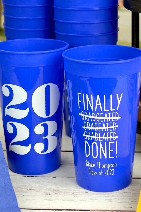 Jumbo stadium cups in Blue with White Imprint, design G1223 on the front and G1216 - 2023 on the back and two lines of text in quick lettering style