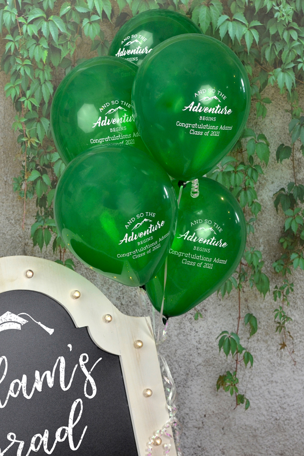 Custom Printed 9 Inch Latex Balloons in Green with White imprint, personalized with G1206 - Adventure Begins design and two lines of text in Adventurous lettering style