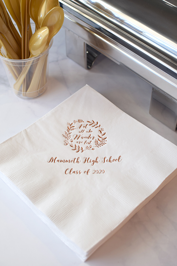White dinner napkin printed with Copper imprint color, G1209 design, and Oscar Script lettering style