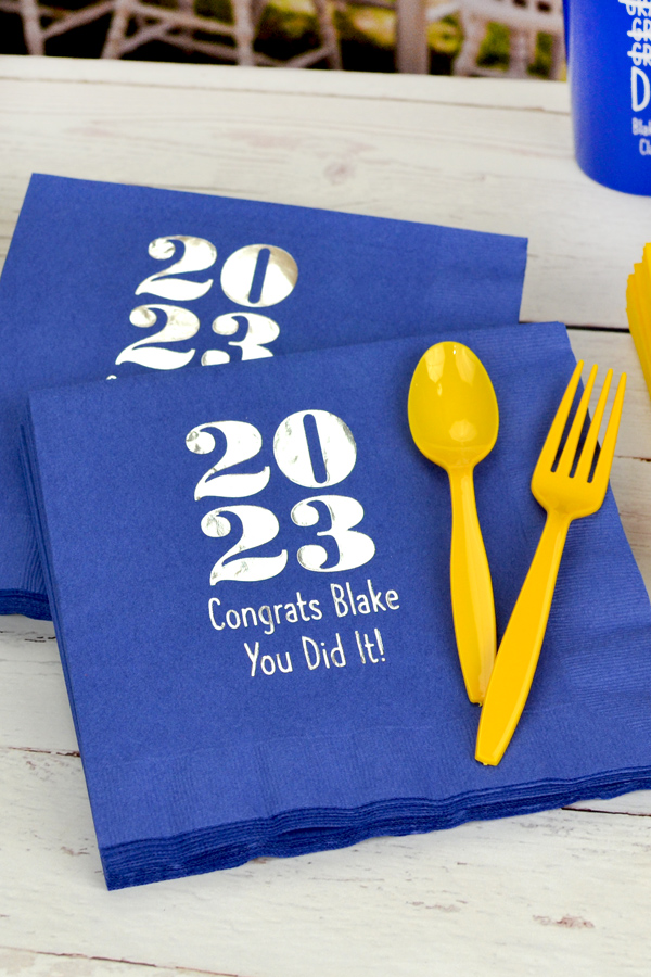 Royal Blue luncheon napkins printed with Silver imprint color, 2023 Bold Graduation Year design, and Quick lettering style