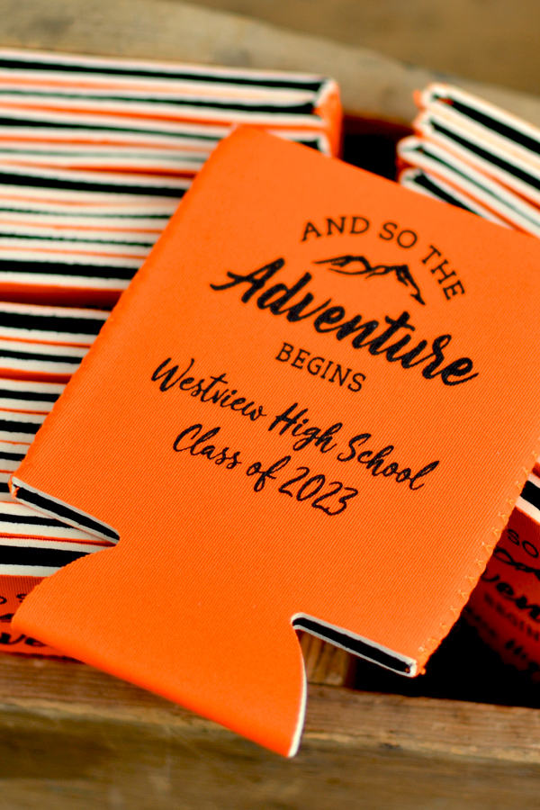 Collapsible neoprene can coolers in orange personalized with adventure begins design and two lines of text black imprint