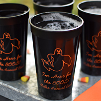 Black 22 oz stadium cups printed with Orange imprint color, 1252 ghost design, and three lines of text in Playful lettering style