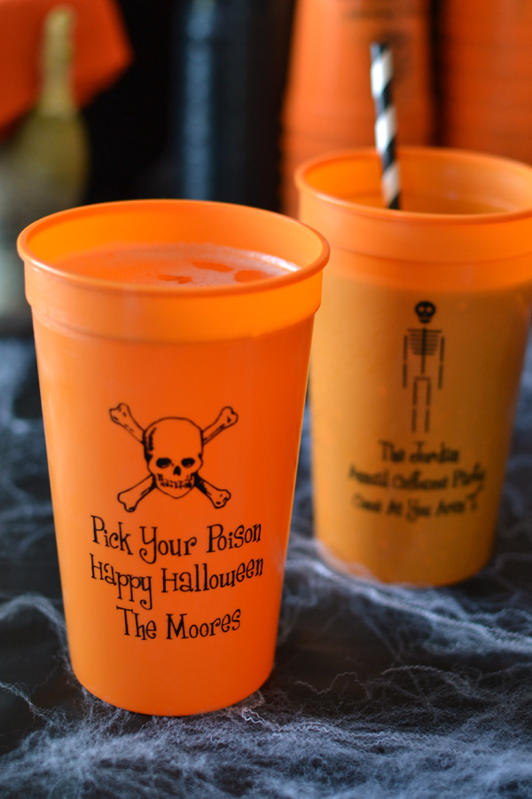 Orange 22 oz stadium cups printed with black imprint color, skull and crossbones design, and three lines of text in Dimwit lettering style