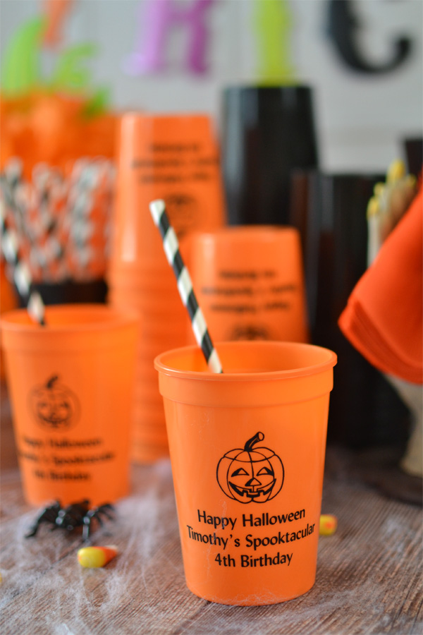 Orange 12 oz stadium cups shown with black imprint color, pumpkin design, and three lines of text in Natural lettering style