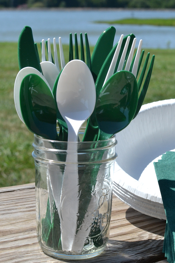 Assorted cutlery in hunter green and white displayed at buffet table