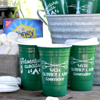Personalized summer party double-walled insulated souvenir stadium cups with optional lids, Green with White imprint, custom printed with SUM115 and SUM125 designs and text in Nutty lettering style