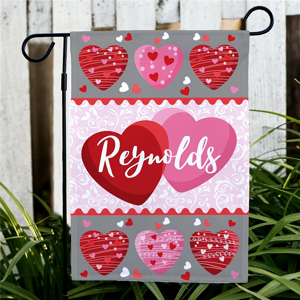 Decorated pink and red Valentine hearts garden flag personalized with family name for Valentine's Day decoration